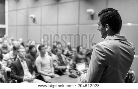 Speaker giving a talk on corporate Business Conference. Audience at the conference hall. Business and Entrepreneurship event. Black and white image.
