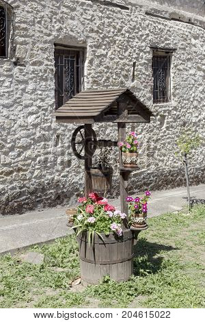 Decorative well with pots and flowers (landscape design)