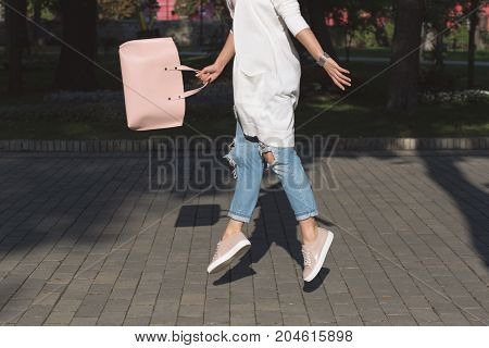 Woman's leggs. Jumping woman with bag. Lifestyle and easeness concept.