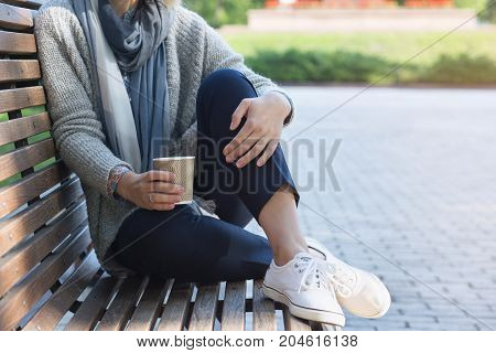 Blond woman is sitting on the bench and holding coffee. Loneliness concept