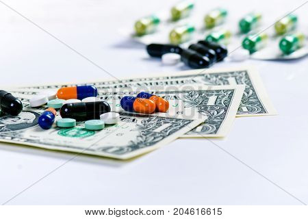 Pharmacy background. Pills on a banknote isolated on a white background. Different types of capsules on dollars banknote. Money and pharmaceutical industry.