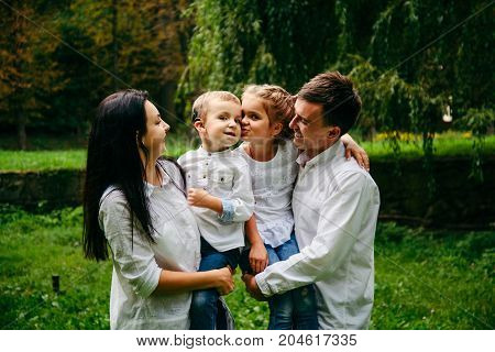 family of four people portrait in city park sister kissing brother
