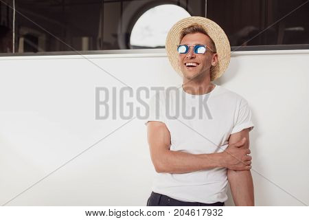 Young casual man in sunglasses and straw hat posing and laughing looking away.