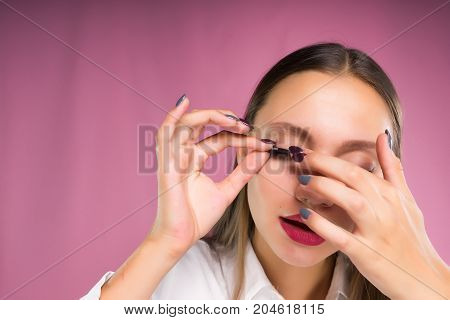 A young woman glues false eyelashes, chooses the type of eyelash extension. Face care, beauty