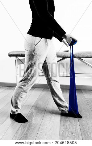 Patient Is Doing Therapy With An Elastic Band For Strengthening Legs In Silhouette. Color And Black
