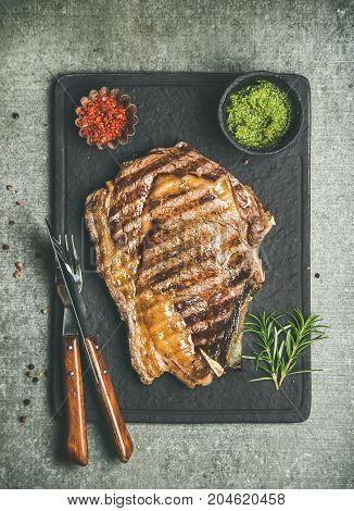 Flat-lay of grilled hot rib-eye beef steak on bone with chimichurri green sauce and hot red chili pepper on black slate board over grey concrete background, top view. Meat high protein dinner concept