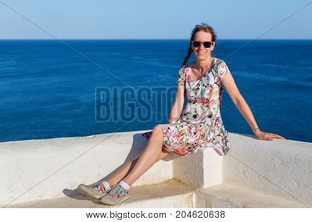 Caucasian middle aged woman as tourist with blue sea