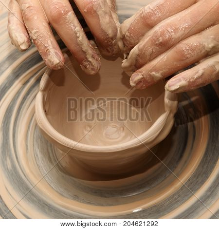 Woman in process of making clay bowl on pottery wheel. Potter at work. Close up view.