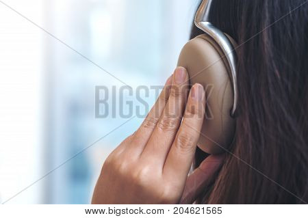 Closeup image of a woman turn back using and holding headphone with feeling relax in modern cafe