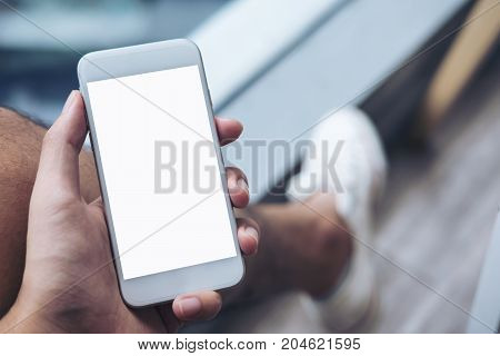 Mockup image of a man's hand holding white mobile phone with blank screen on thigh with white canvas shoes in modern cafe with feeling relax