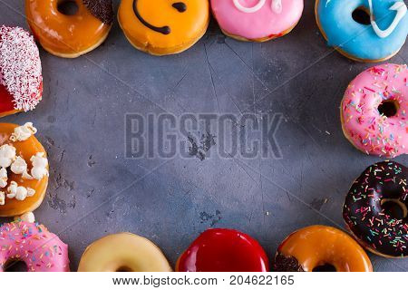 sweet doughnuts on gray stone background frame with copy space