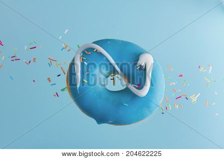 one flying sweet doughnut with sprincles on blue