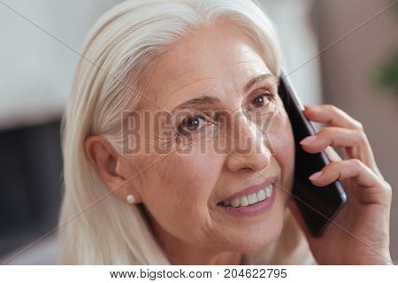 In touch with you. Close up of a cheerful retired woman smiling and talking on phone while having a nice conversation