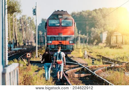 A guy and a girl are walking towards the train by a locomotive on the railway