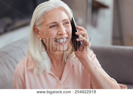 Chatter box. Close up of a cheerful smiling aged woman sitting on the couch and having a pleasant conversation on phone while at home