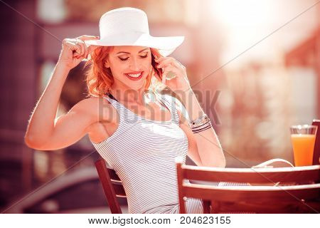 Portrait of smiling lady in dress sitting in restaurant and talking on her cellphone.