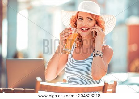 Woman with juice and laptop on table. Portrait of smiling lady in dress sitting in restaurant and talking on her cellphone.