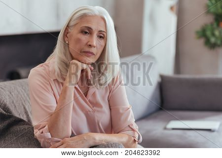 First sign of depression. Waist up of a thoughtful aged woman sitting on the couch and thinking about her life while feeling sad