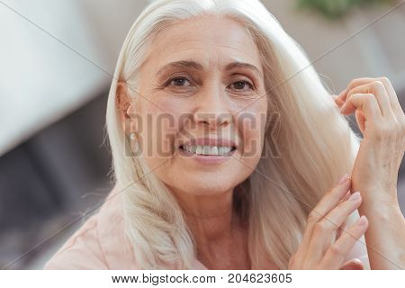 Sincere glance. Close up of a nice aged woman smiling and posing while expressing joy