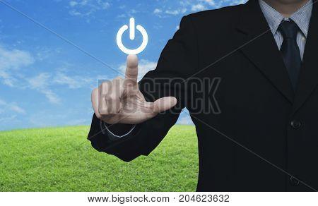 Businessman pressing power button over green grass field with blue sky Start up business concept