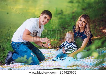 happy family walks in the park, sit on the bank of the lake and admire a decline. Baby boy birthday.