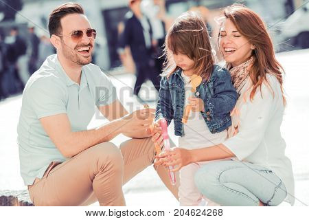 Happy family with one child having fun together in summer city .