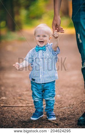 father walks with the little son in the park, the kid takes the first steps