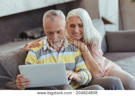 Long lasting relationships. Waist up of a cheerful loving aged couple using their laptop and surfing the Internet while resting at home