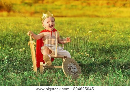 the king the child astride a horse plays with a sword. Little Prince with a crown on the head and in a red raincoat.