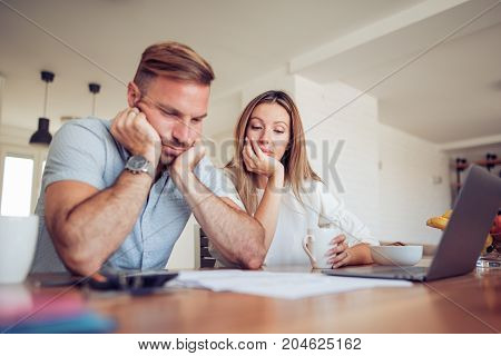 Couple having problem with bills.Worried young couple doing their accounts in the living room.