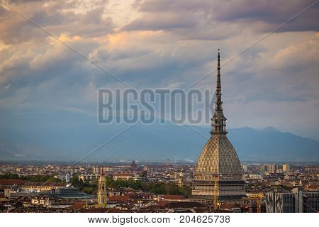 Cityscape Of Torino (turin, Italy) At Dusk With Dramatic Sky Over The Alps. The Mole Antonelliana To