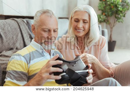 Smart technologies. Positive impressed aged couple testing VR glasses and sitting on the floor while resting at home