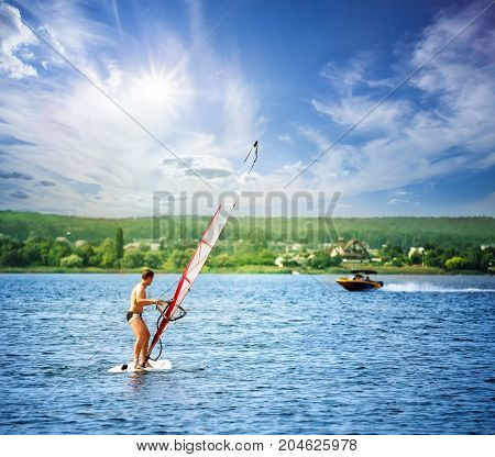 Windsurfer on board with white sail under the bright sun. Summer landscape. The concept of freedom and movement.