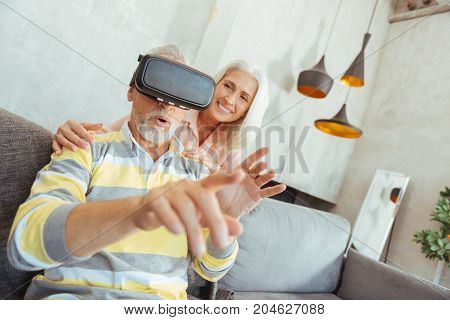 Virtual touch. Close up of a retired man sitting on the sofa and trying up VR glasses while his wife standing behind