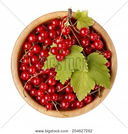 Red currant berries in wooden bowl isolated on white background. Top view.