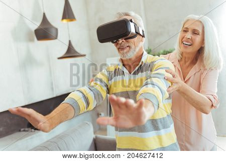 New innovation. Waist up of cheerful aged man testing VR glasses with his smiling nice wife while spending time with pleasure