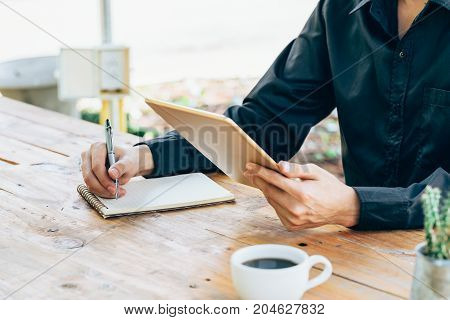 Business Man Hand Holding Tablet And Writing Notebook In Coffee Shop.