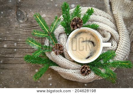 cup of coffee stands on a wooden table. cosy warm knitted plaid, branches and cones