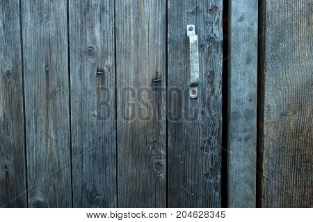 Beautiful old rustic wooden barn door with a handle. Close up