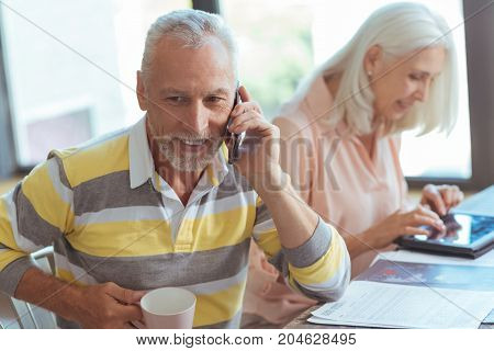 In touch. Positive handsome retered man talking on smart phone and drinking tea while his nice wife using tablet in the background