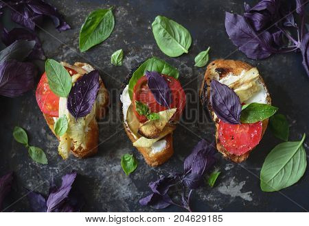 Canapes with cream cheese tomatoes and basil view from above flat lay