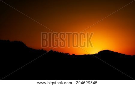 Sunset in a mountains. Sun is hiding behind the mountains