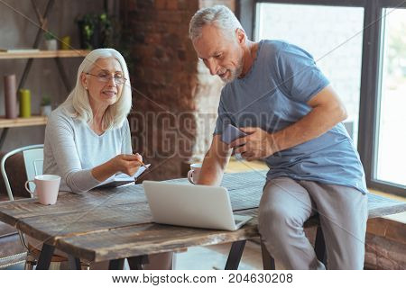 Lets discuss it. Nsce elderly couple using laptop while browsing the web at home