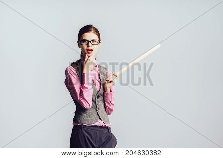 Surprised young woman professor  student holding a ruler in her hand and pointing at something in surprise
