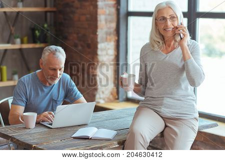 Happy to hear you. Cheerful aged beautiful woman talking on smart phone and drinking tea while her husband using laptop