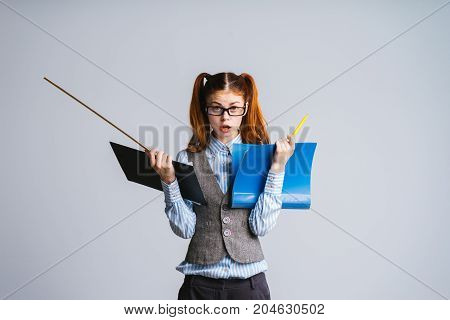 An evil teacher  student with folders and a ruler in her hands looks indignantly at the camera. Tired of learning, stress