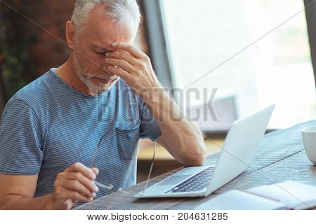 Take care of your health. Waist up of a sick aged man sitting at the table and suffering from a headache at home