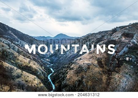Natural landscape with river canyon in mountain valley with text Mountains. Travel or wonderlust inspiration concept