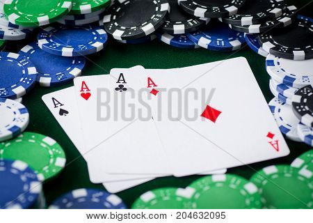 four kings on green background with poker chips.