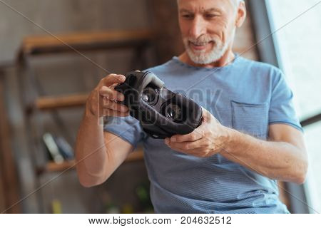 Lets try it in life. Close up of a VR device in hands of a positive bearded aged man holding it and going to test while smiling